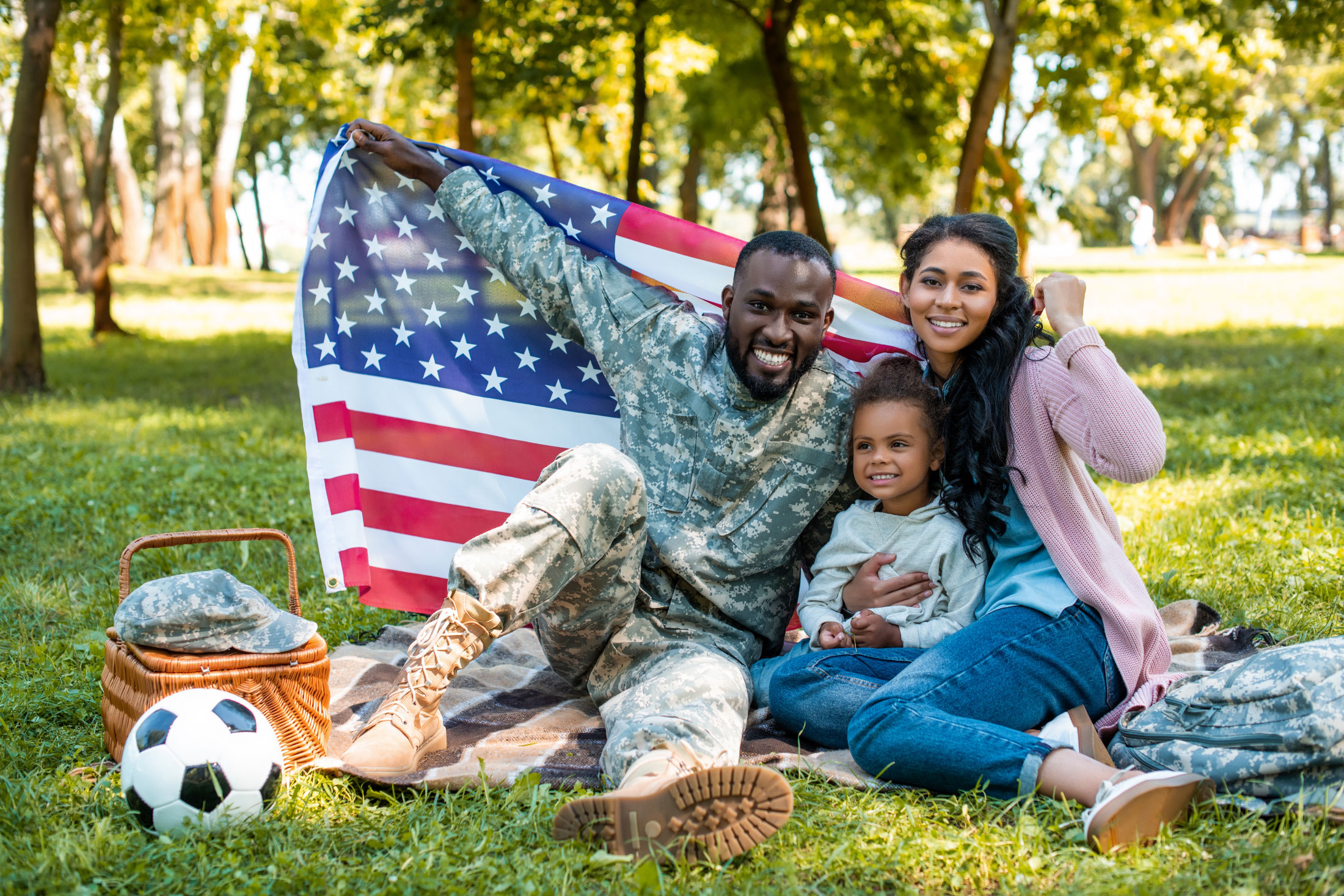 Military family holding an American flag at a park.