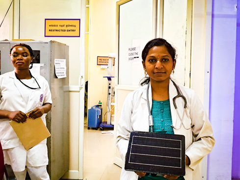 A doctor in a maternity ward holding a Clarity Node used for air quality monitoring in Bengaluru.