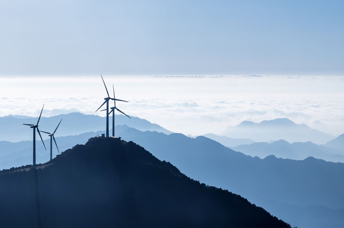 Wind turbines stand on a hilltop, a symbol for greater action towards improving air quality and mitigating climate change such as through the adoption of clean energy.