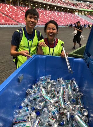 Two volunteers pointing the drinking cans
