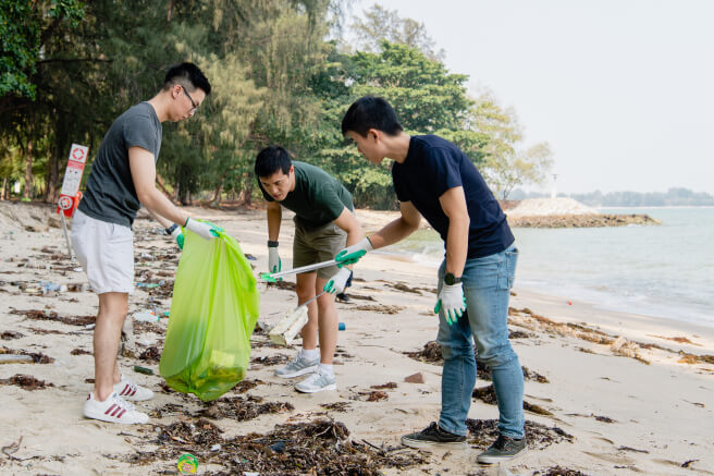 3 people picking up trash at the beach