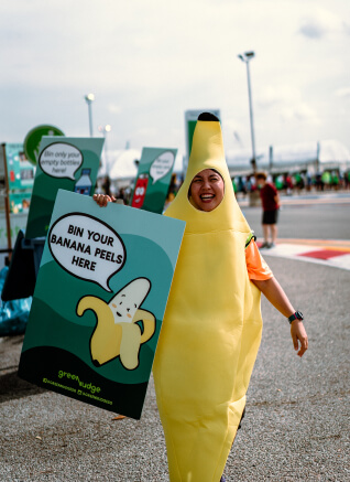 A volunteer in the banana mascot and holding a board.