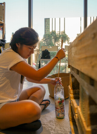 A lady holding a bamboo stick to make ecobrick.