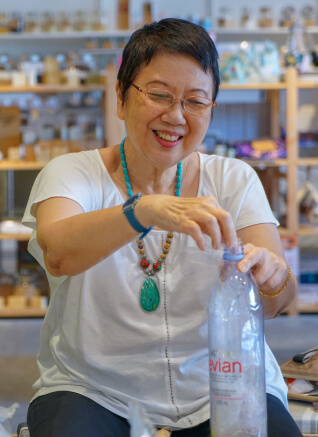 A lady smiling while stuffing plastic material into a plastic bottle to make ecobrink
