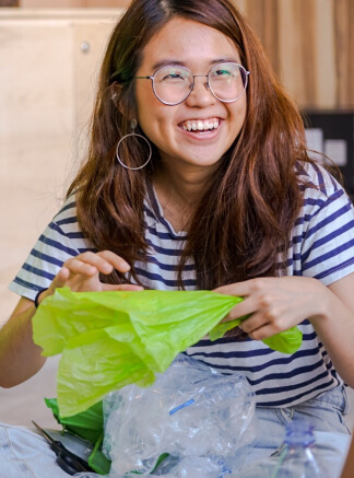 A lady smiling with a plastic bag on hand.