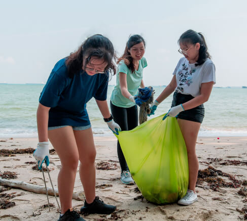 Three ladies picking up trash at the beach.