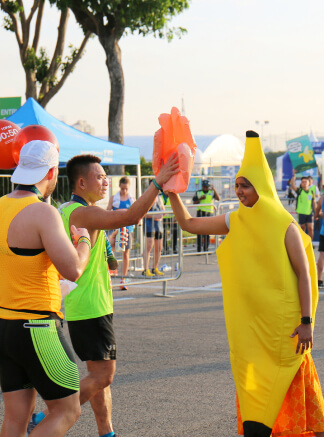A volunteer in banana mascot high-five with participants.
