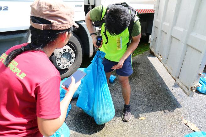 Volunteer weighing the banana peels in a trash bag.