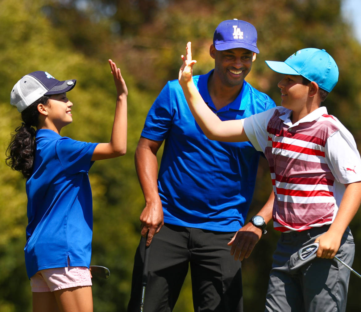 Happy family on a golf course giving high fives.