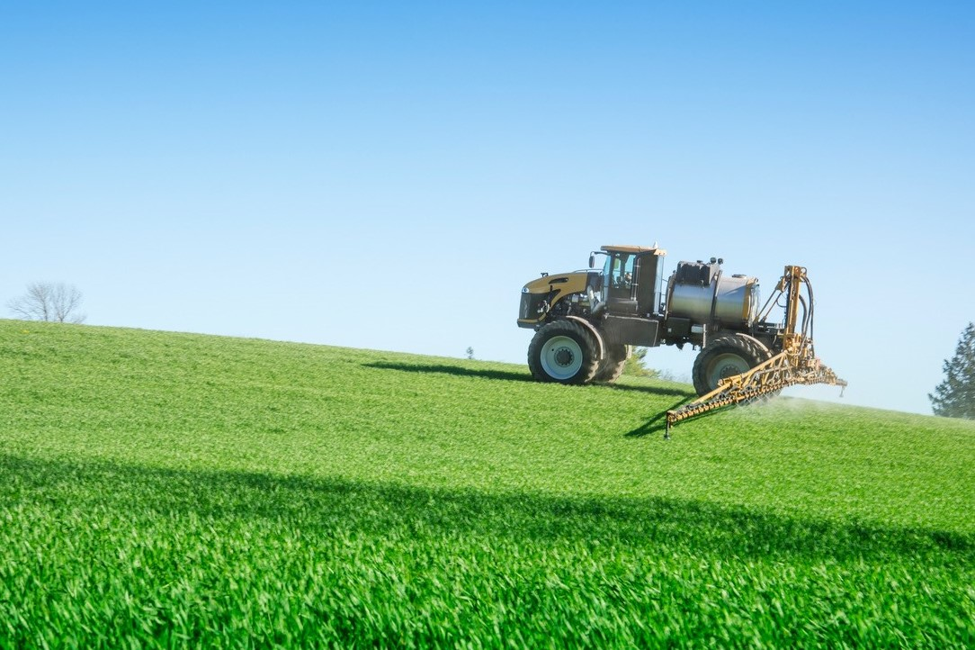 Image of single yellow ground rig spraying green crops as it climbs a hillside