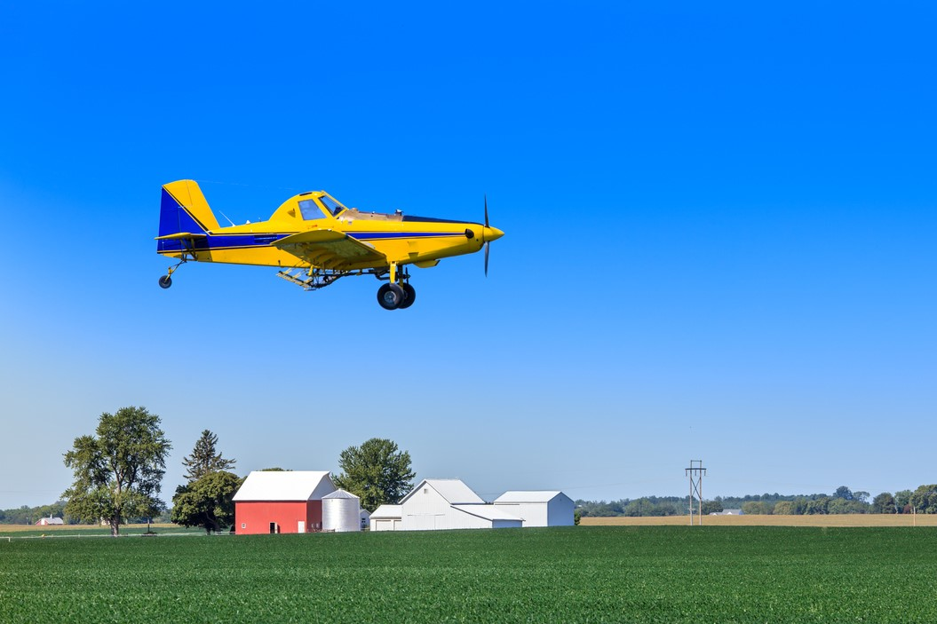 Image of a single yellow and blue Air Tractor airplane flying over a green soybean field with barn and trees in background