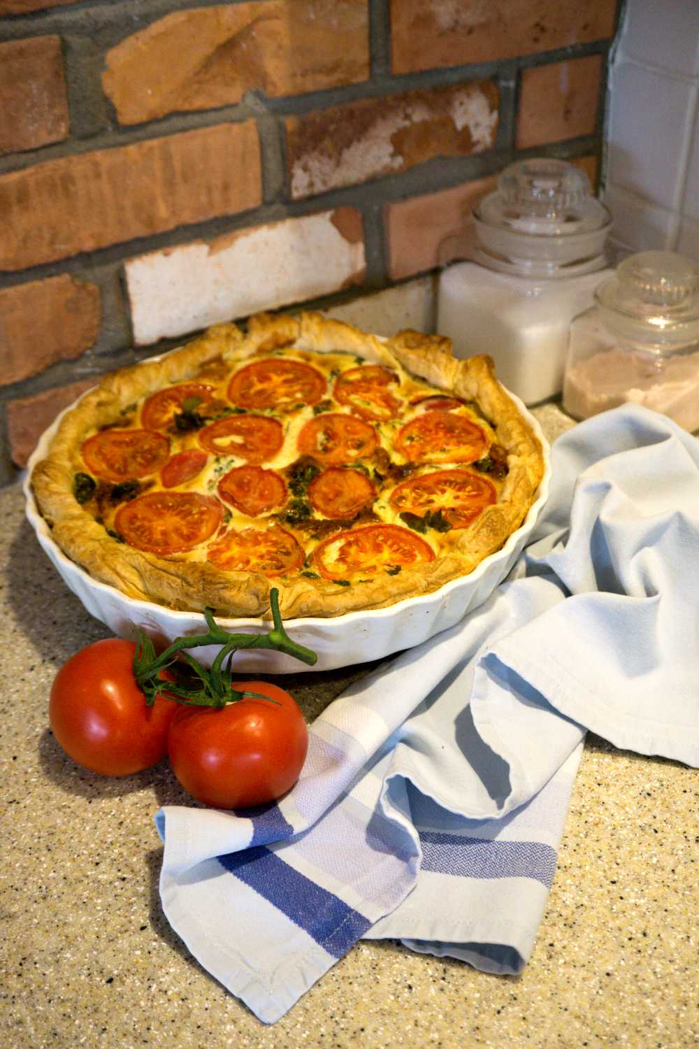 Quiche and tomatoes in front of a rustic brick wall