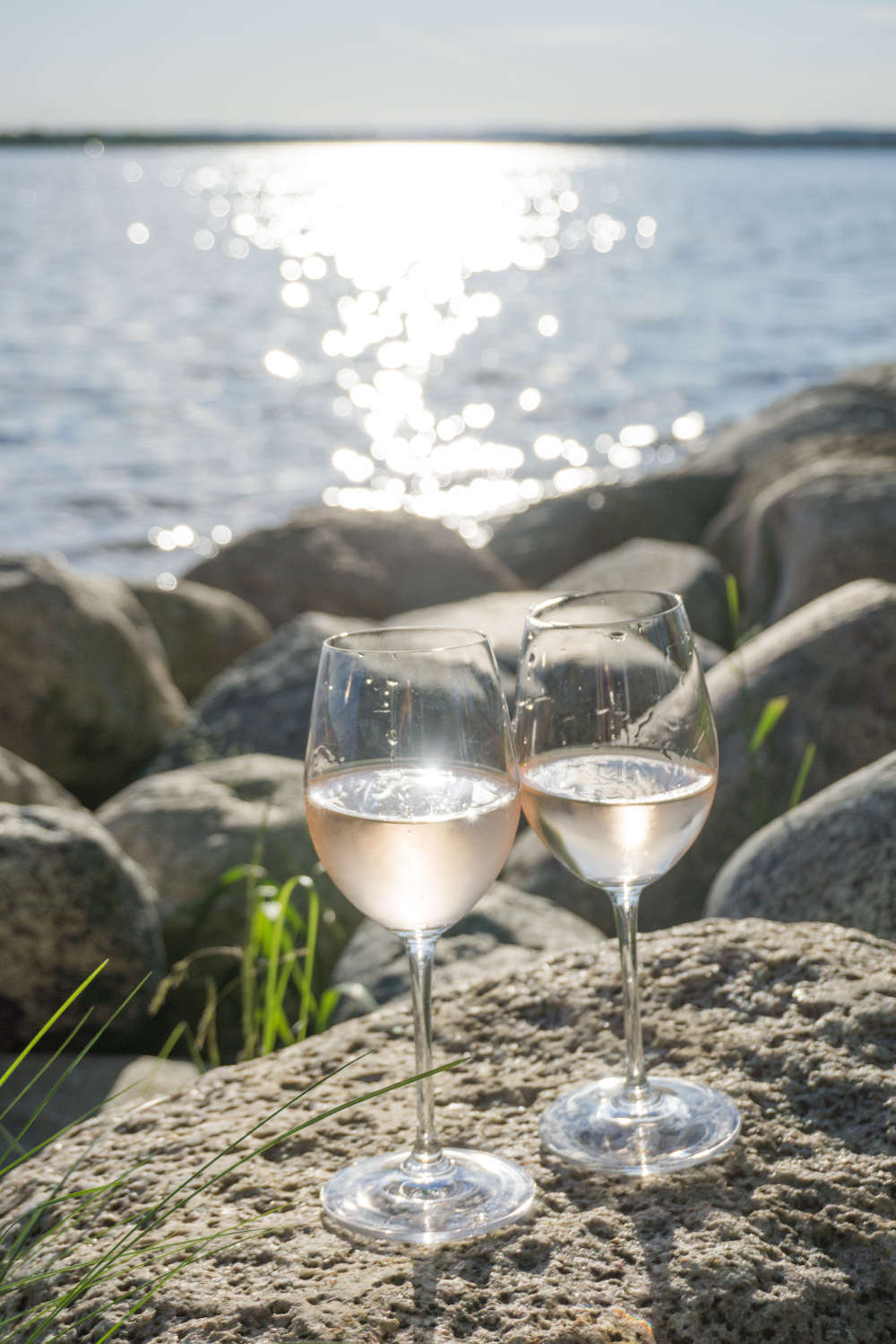 Two glasses of wine on rocks in front of Wellers Bay at The Empty Nest in Prince Edward County