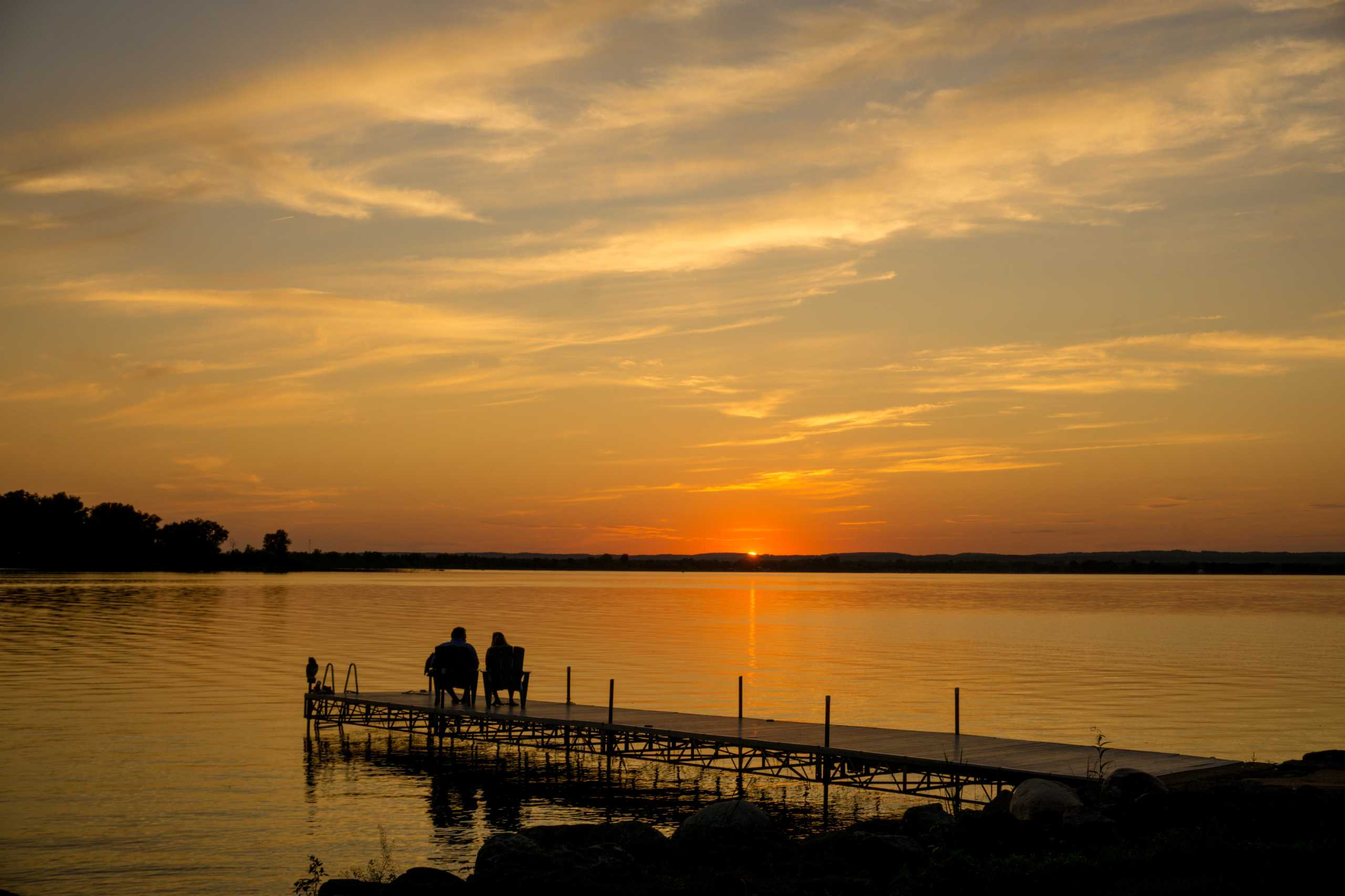 Man and woman sitting on a dock watching the sun set over Wellers Bay at The Empty Nest in Prince Edward County