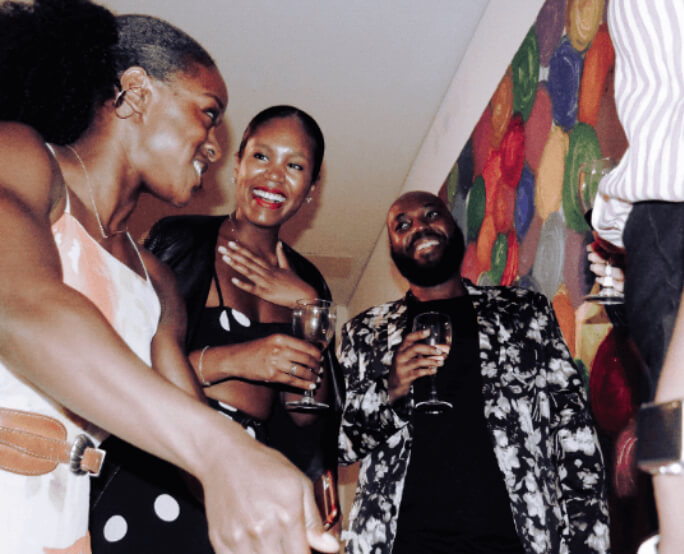 Two black woman and a black man socializing at a party