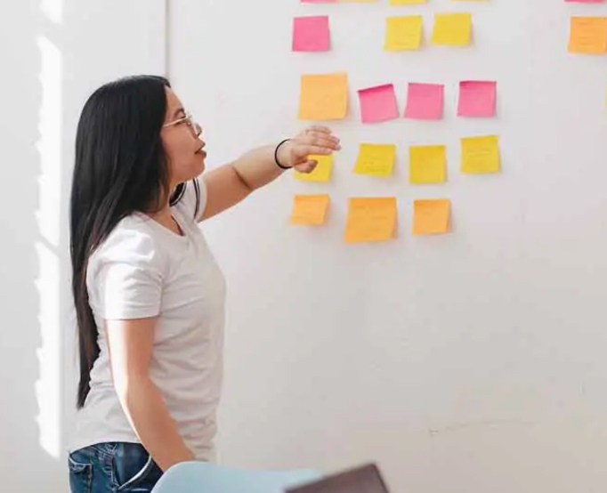 woman posting posted notes on the whitboard