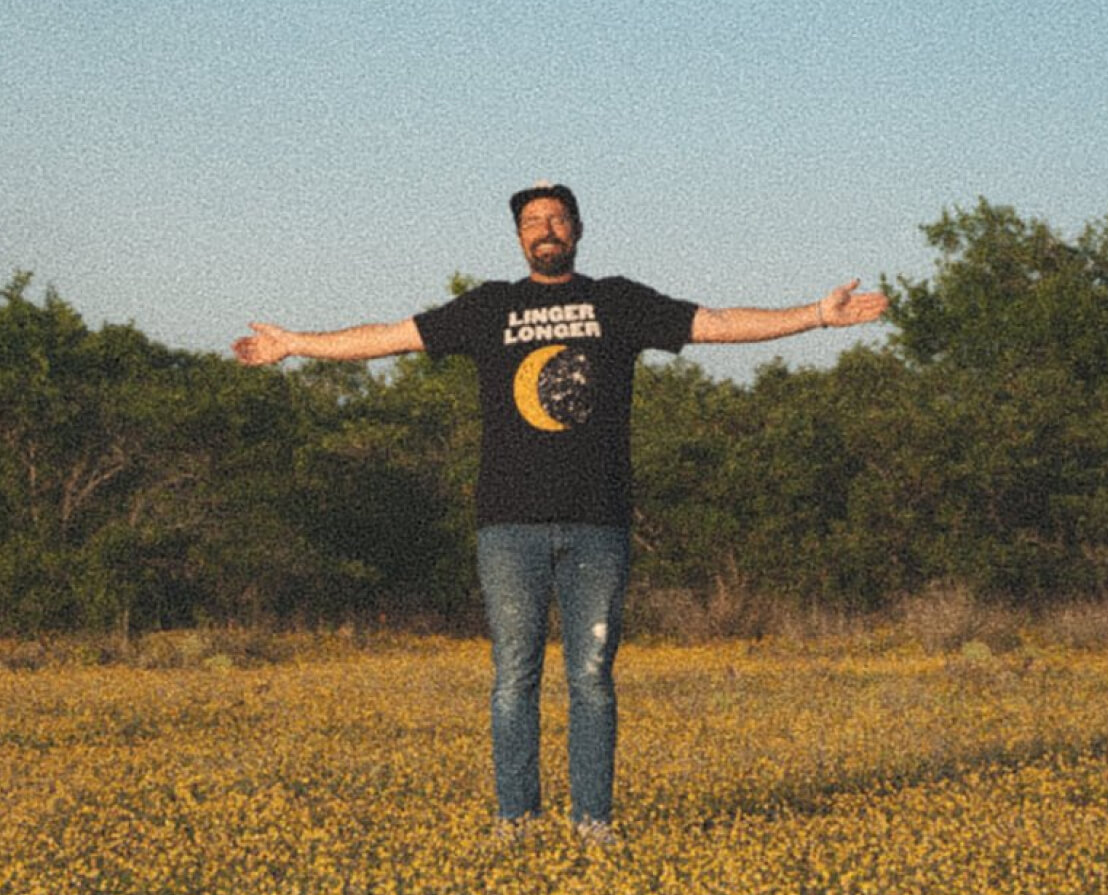 """Image of a man with his hands spread out in a field with a shirt that says, """"Linger Longer"""" on it representing the brand Uncle Bobby"""