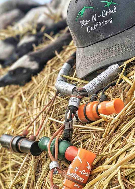 rise n grind hats and duck calls on hay bail