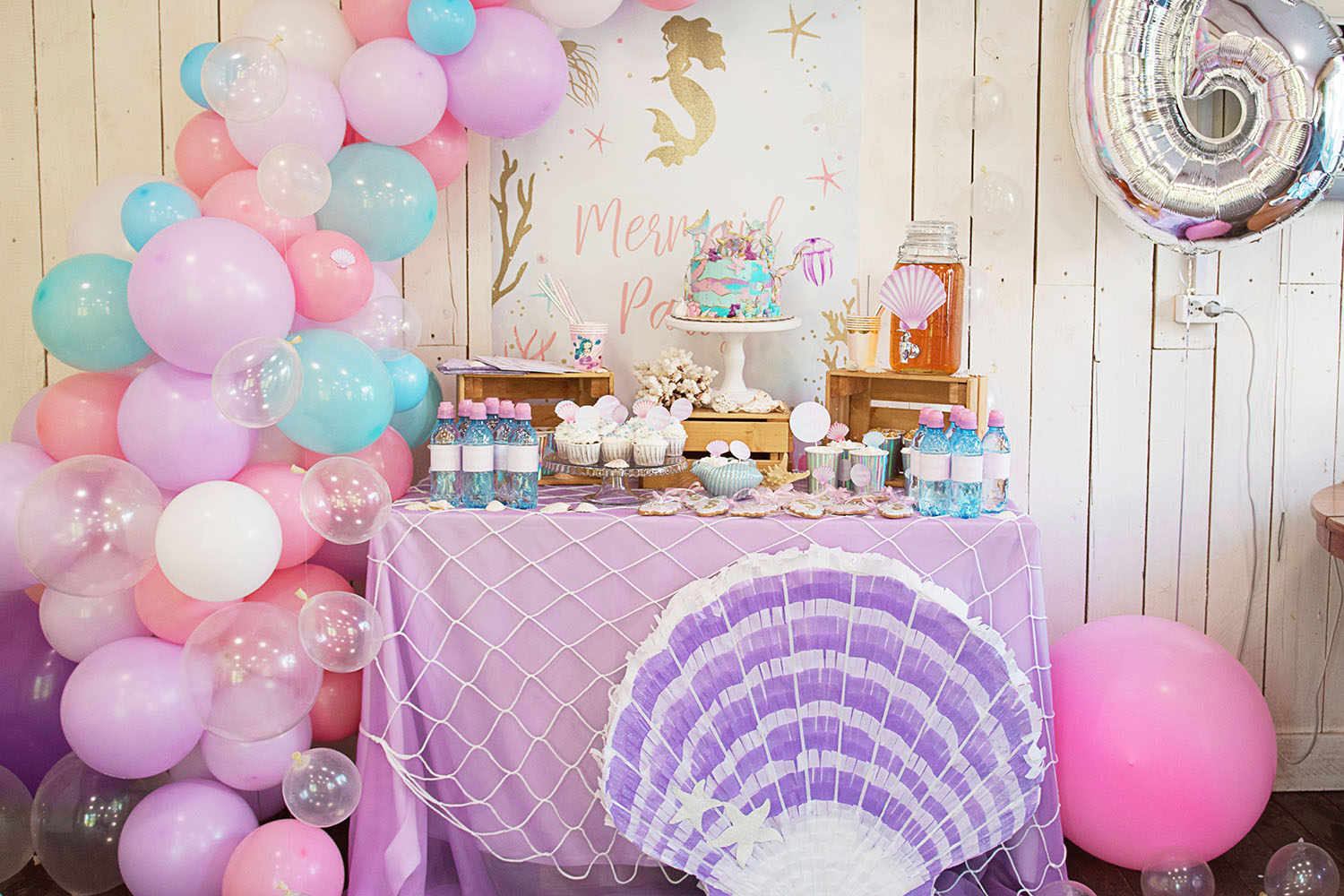 Mermaid bachelorette party dessert table with pastel balloons