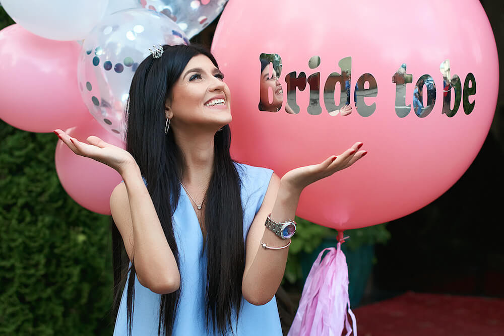 When to have a bachelorette party: Smiling bride to be surrounded by pink and white balloons