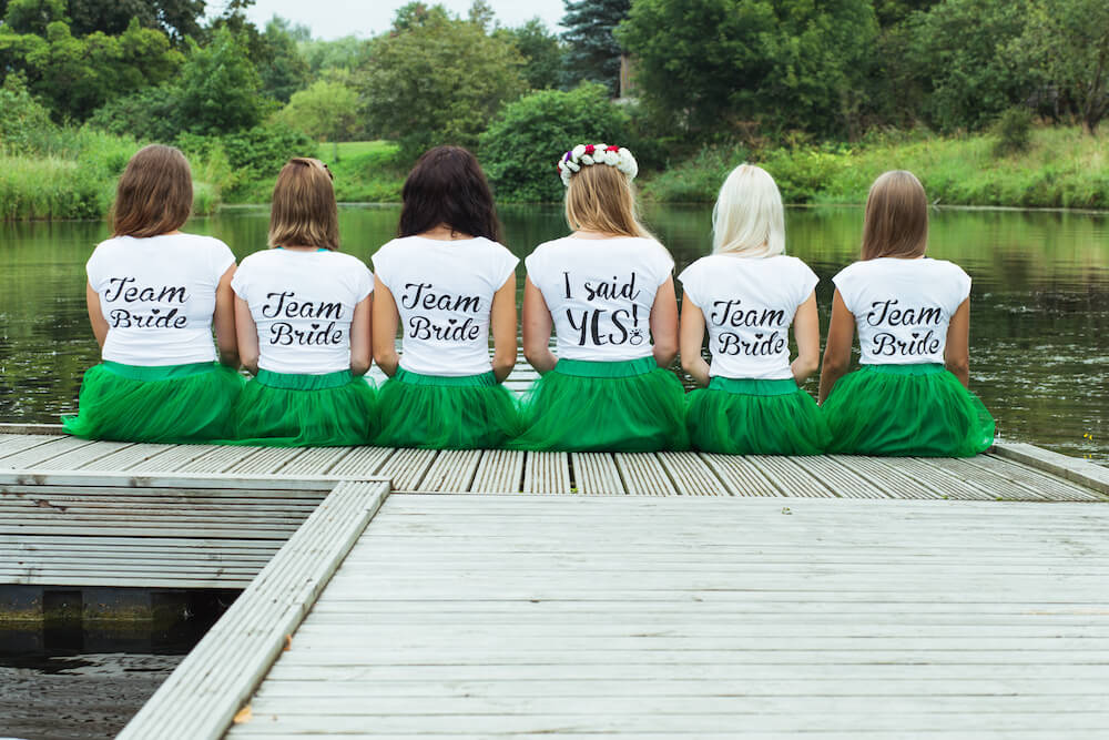 When to have a bachelorette party: Bride and bridesmaids sitting at the dock while wearing matching outfits