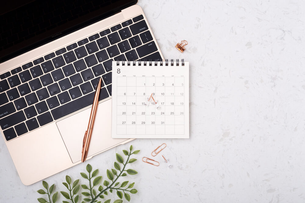 Laptop, pen, pins and a calendar on a white surface
