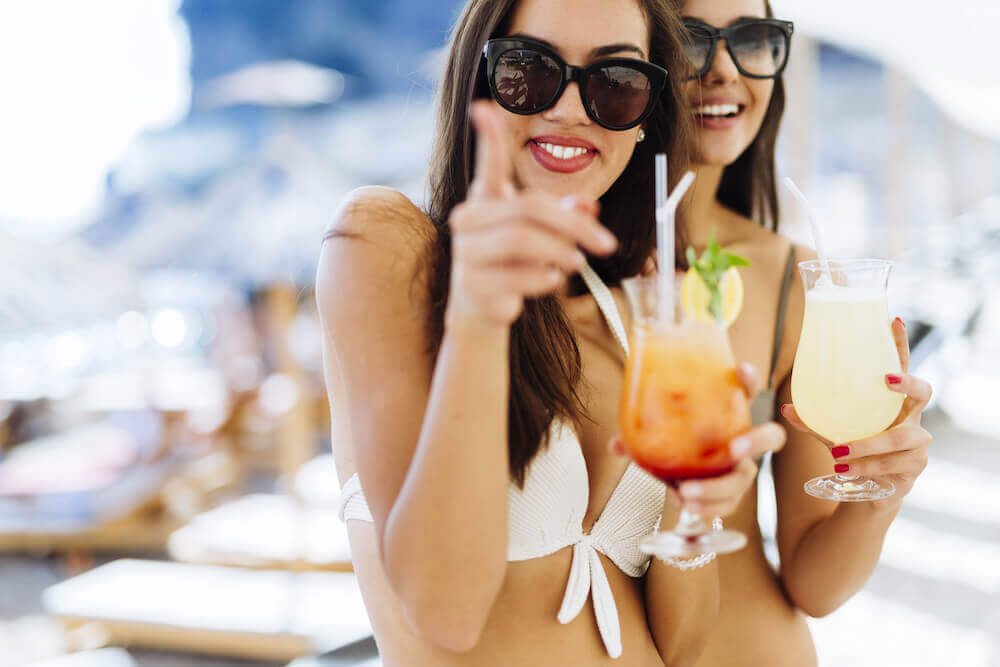 Two smiling women in swimsuit having fun while holding their cocktail drinks