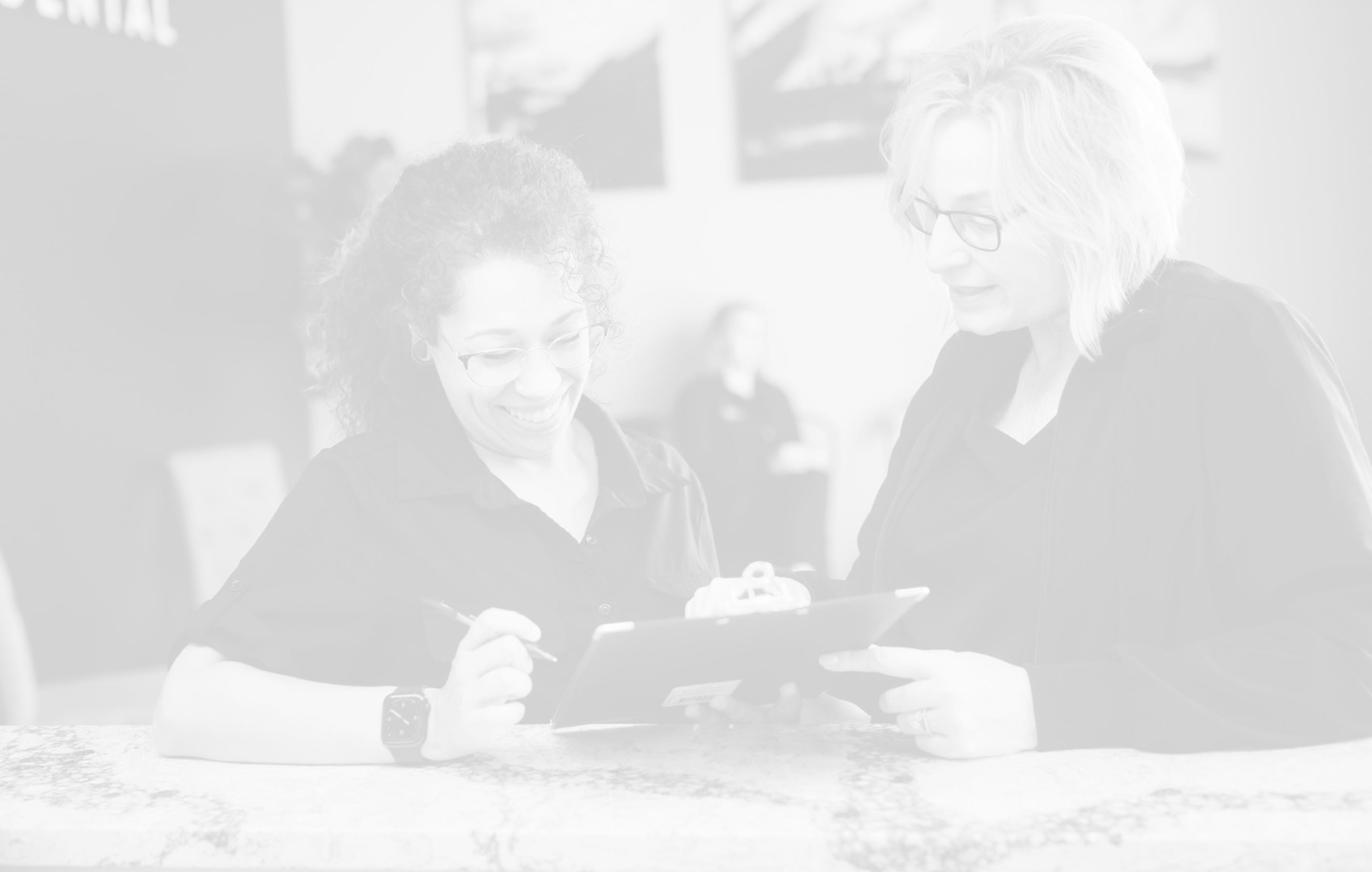 Photo of a team member and a patient looking at a clipboard