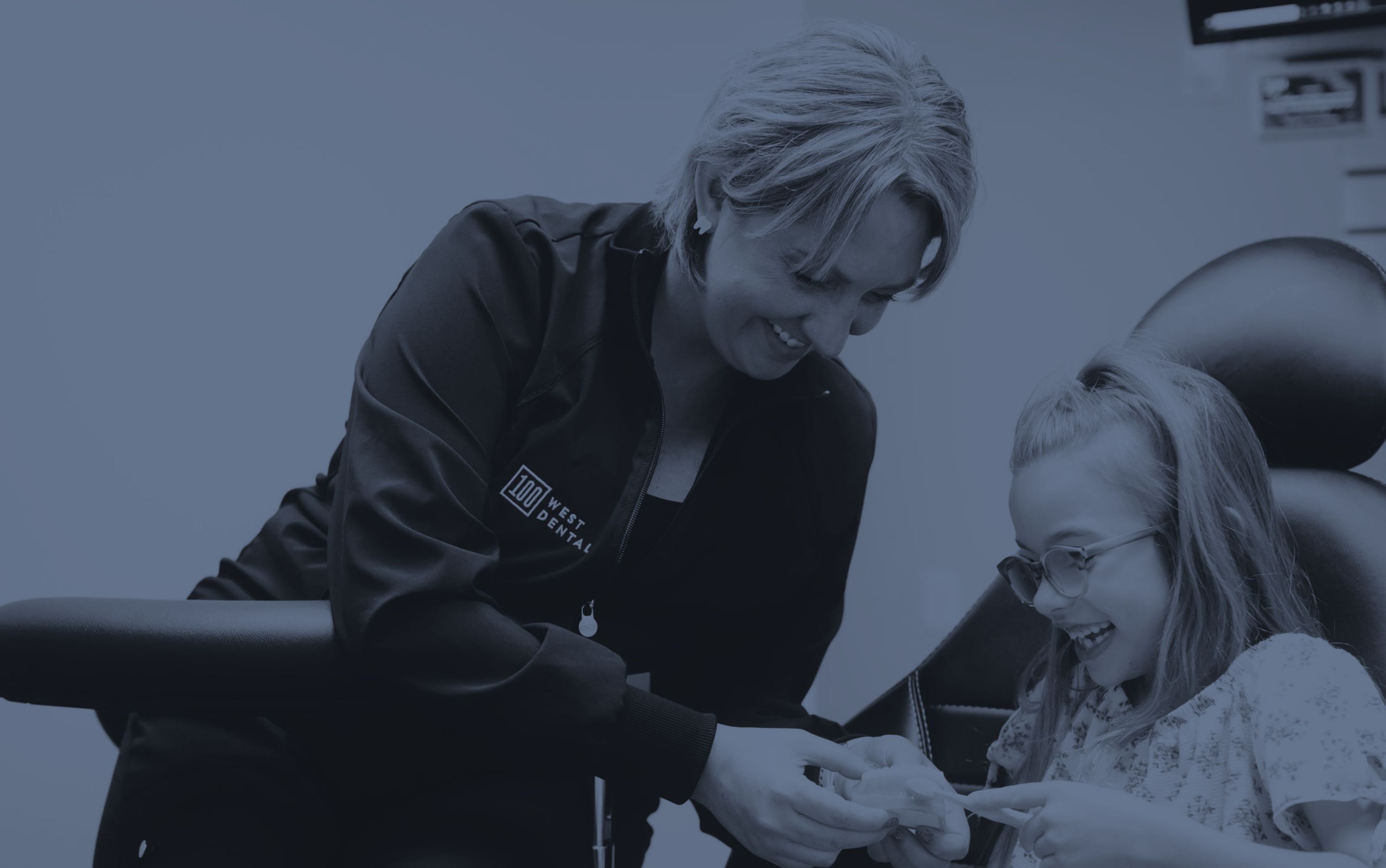 Photo of a team member showing a young patient how to brush properly on a dental model
