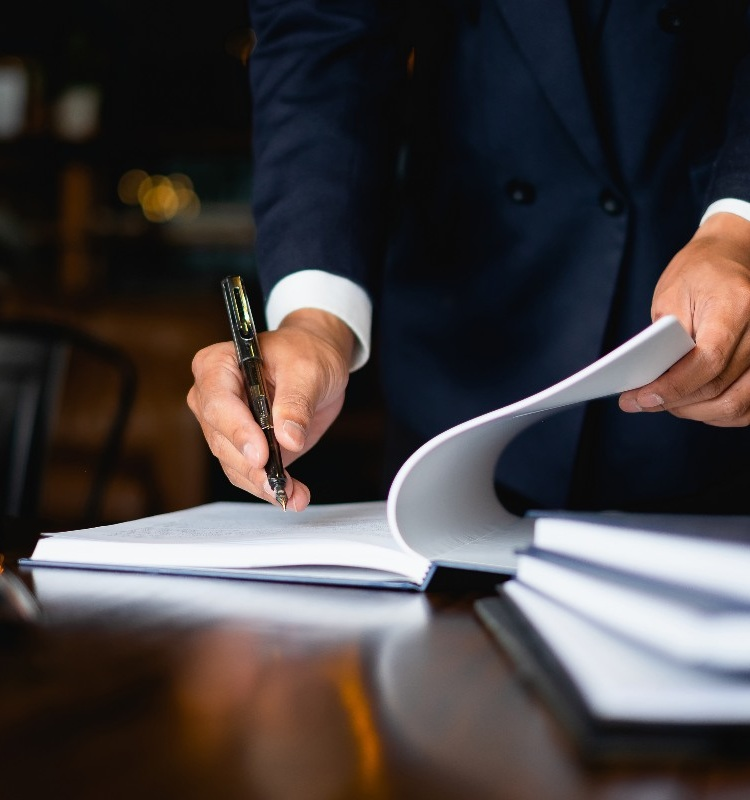 man in suit signing paper