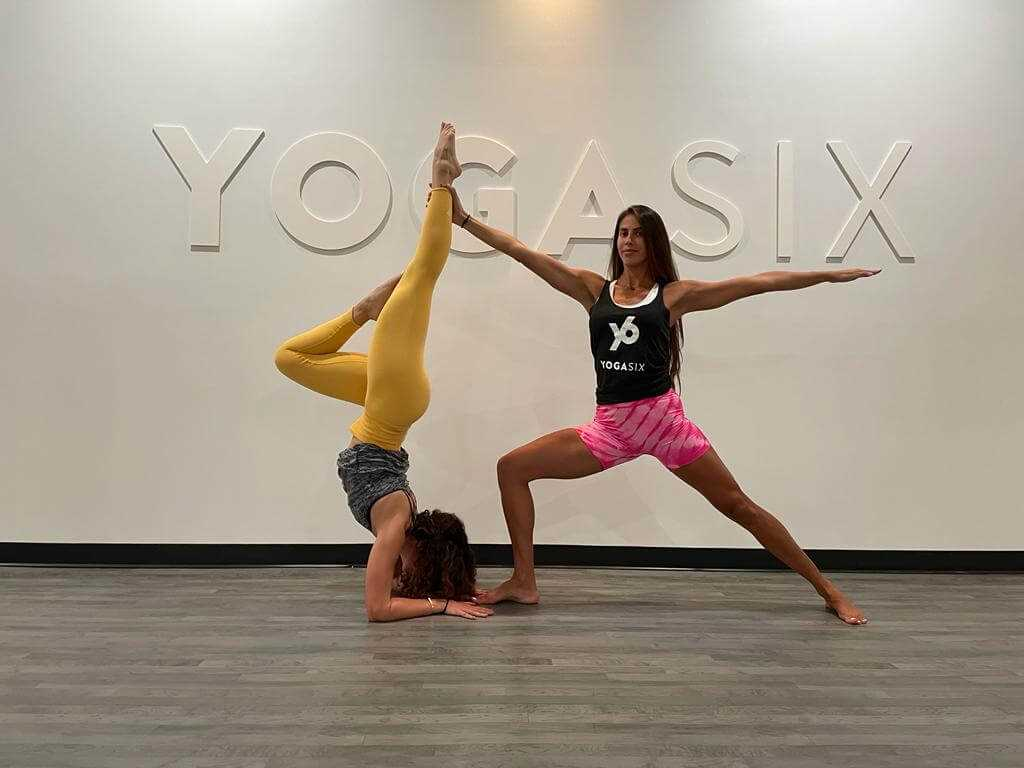 Two girls holding yoga poses in front of YogaSix sign