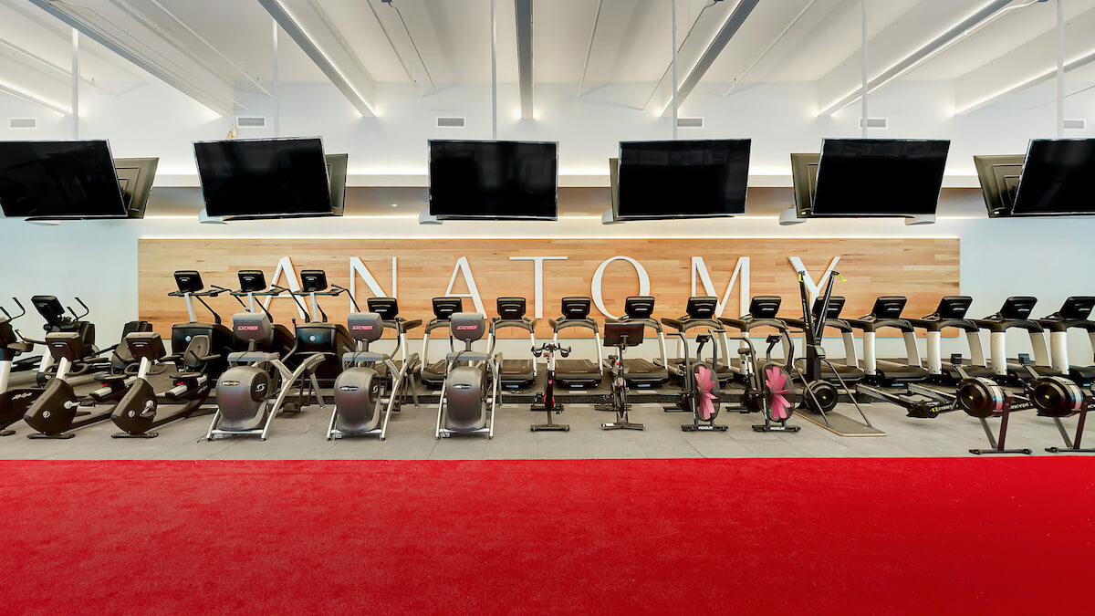 photo rendering of the inside of a gym with a turf, treadmill, and tvs