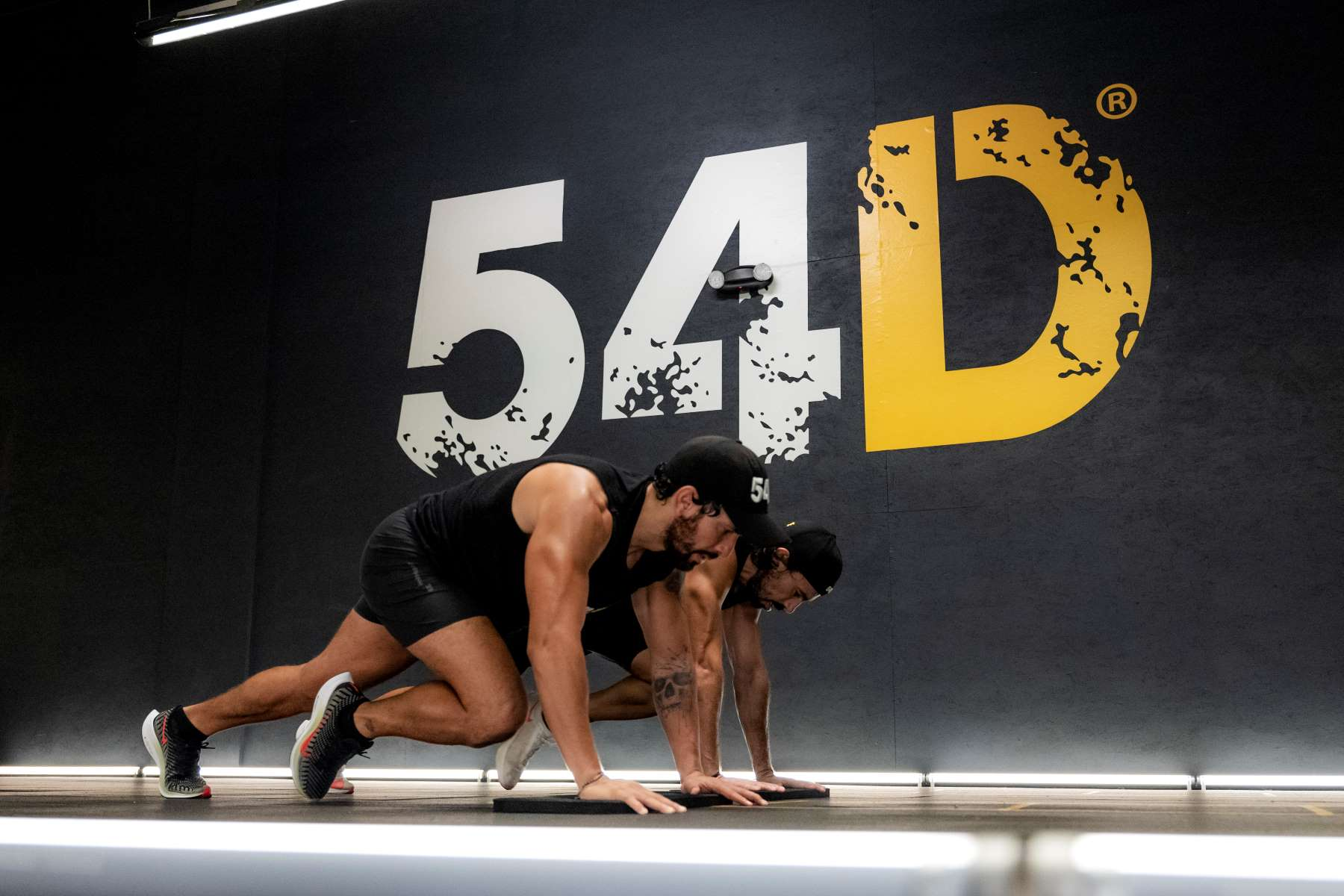 54D Trainers Working Out in Front of Logo