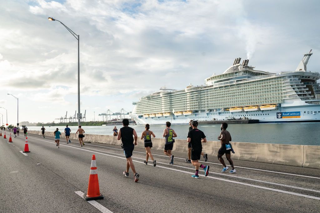 people running on a road next to a cruise ship