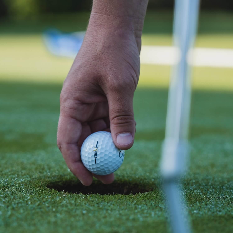 golfer picking up golf ball
