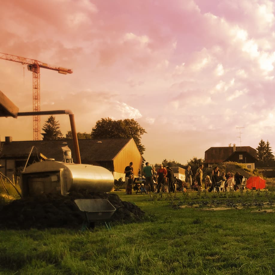 Hofstelle Kerschbaumerhof e.V. Juni 2021 Menschen arbeiten gemeinsam in der Solidarischen Landwirtschaft in Grafing man sieht  die grüne Fläche auf der Hofstelle und eine Gruppe an Menschen im Vordergrund steht ein Regenwassertank
