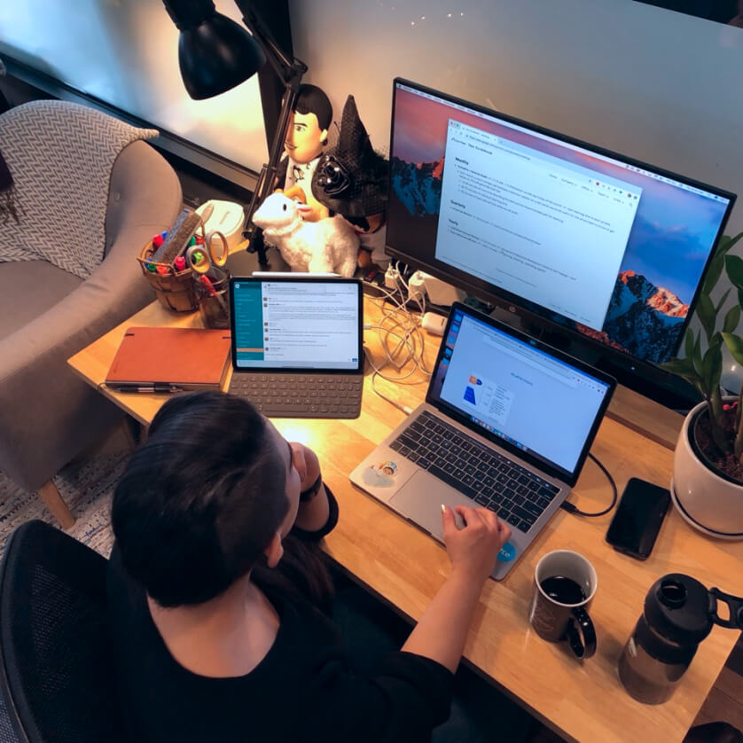 Image of person working on wooden desk with laptop and tablet.