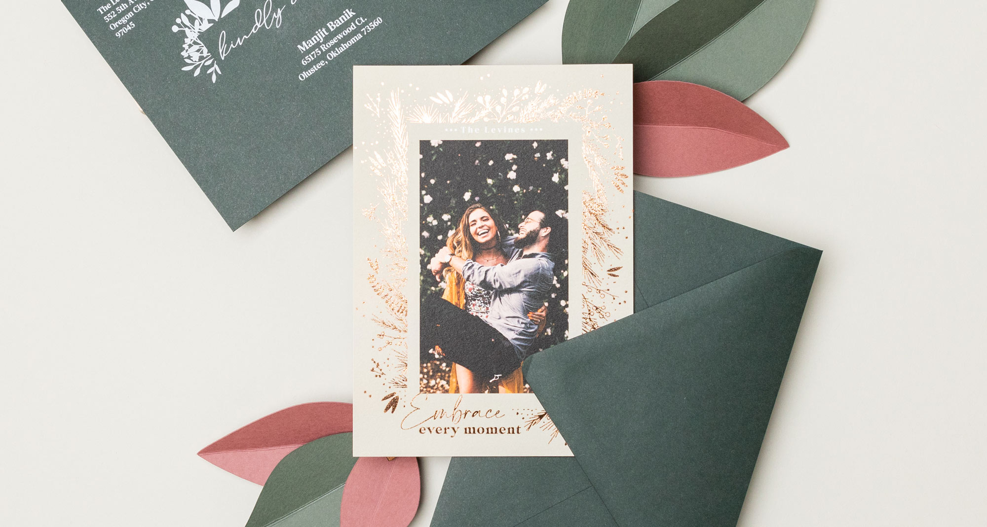 Foil-pressed holiday card with recipient address printing in white ink on dark green envelopes by WHCC