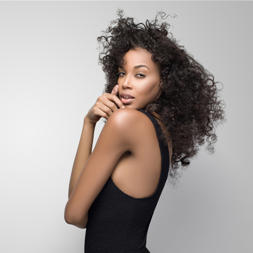 Dark skinned woman with slim body and curly hair.