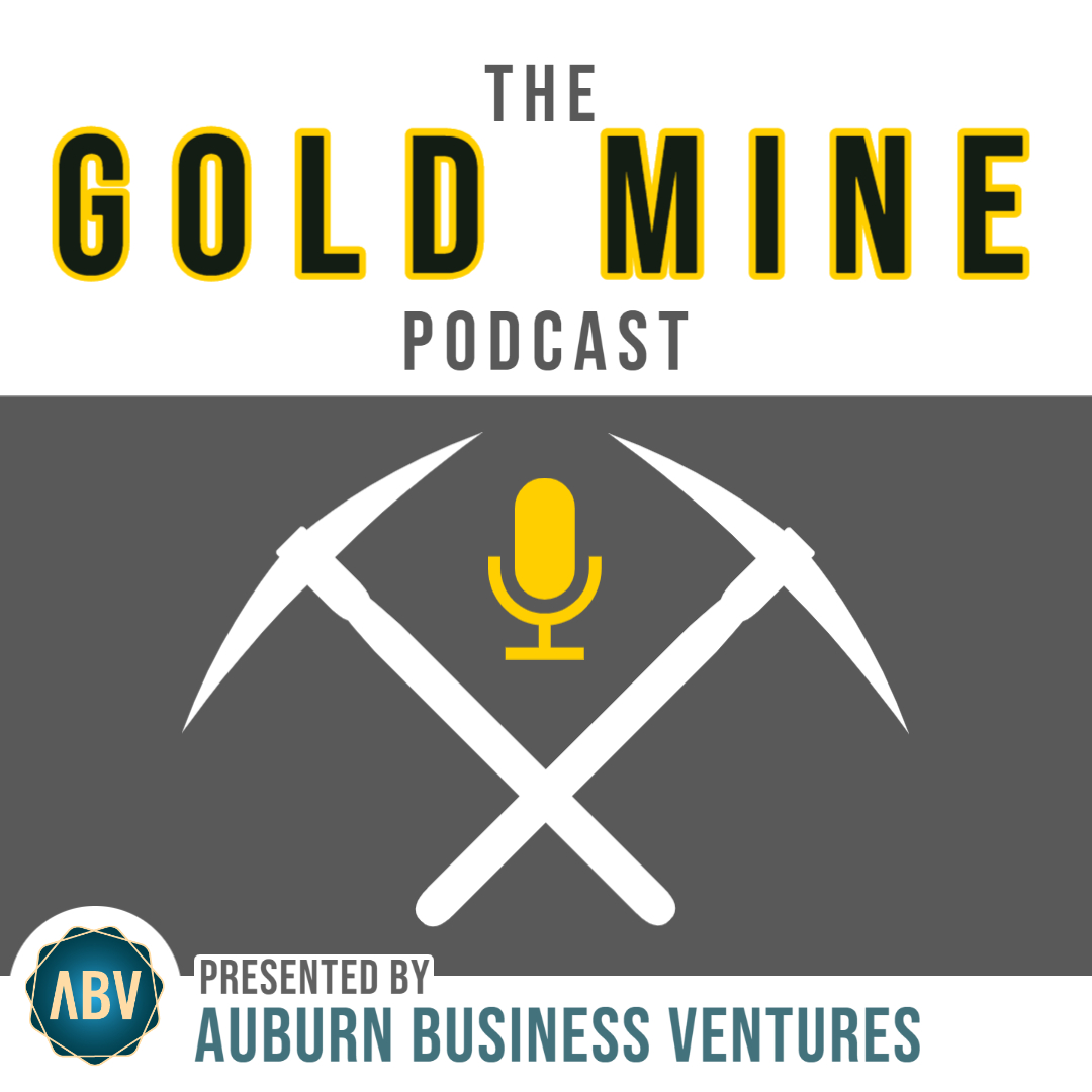 A white square with a grey band across the middle. The Gold Mine Podcast on the top white background, and two pick-axes and a microphone on the grey band.