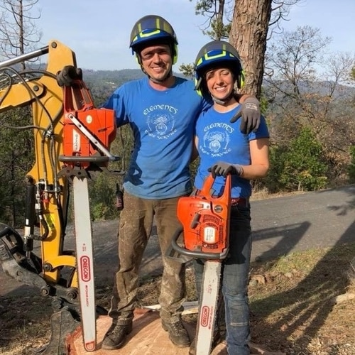 Element's Tree Service Jeremiah and Angelina standing with hard hats and chain saws.