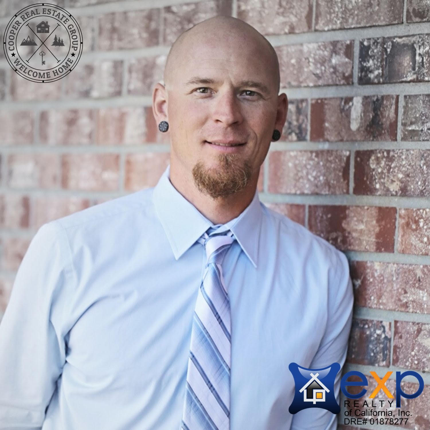 Realtor Justin Cooper leaning against a brick wall in a shirt and tie.