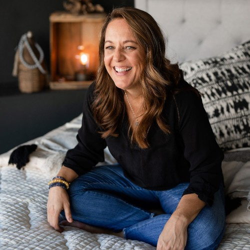 Brandy Alvis, owner of Sage Sleep Organics sitting crossed legged on a bed with a radiant smile.
