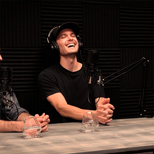 Cody Monroe Sitting At Podcast Recording Table With Headset and Microphone, laughing with eyes closed