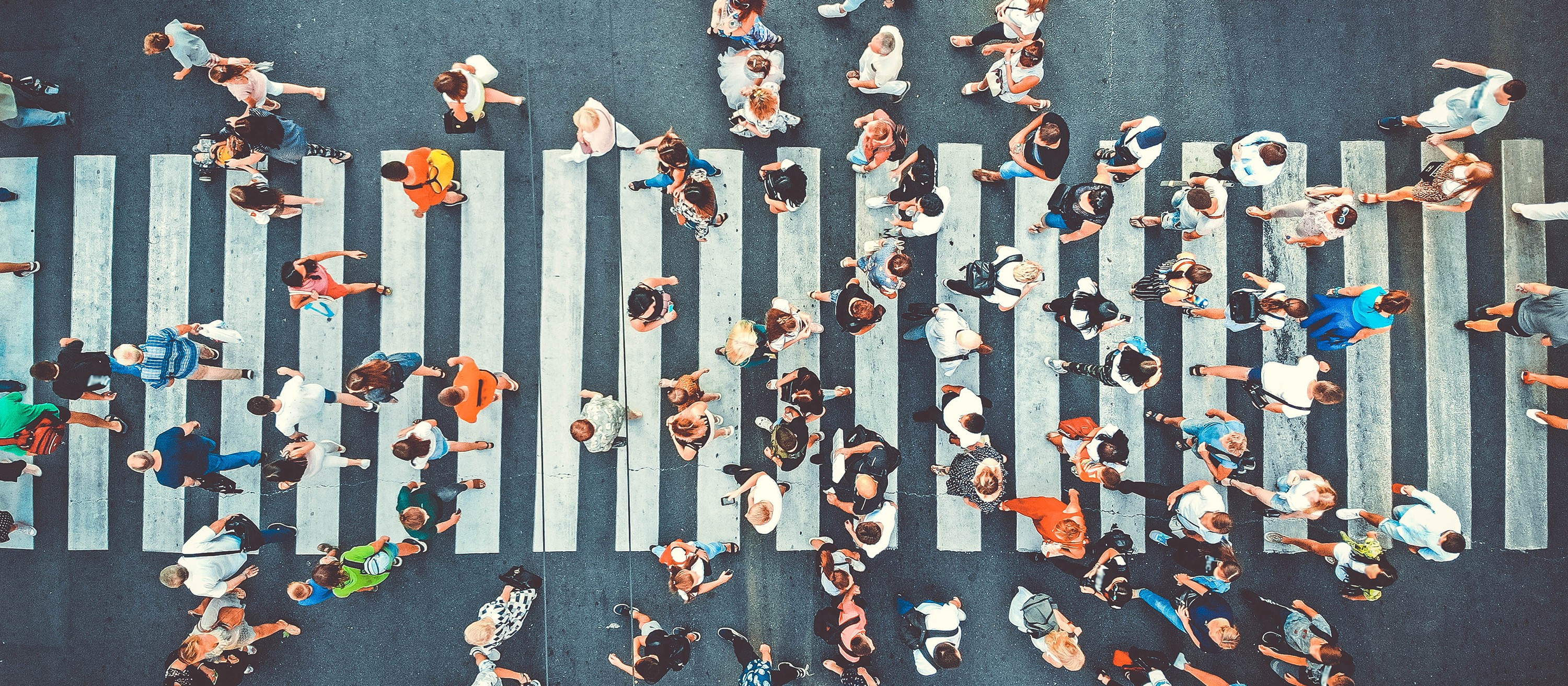 Busy city crosswalk view from above, representing the vulnerabilities large cities face as centralized systems in a pandemic.