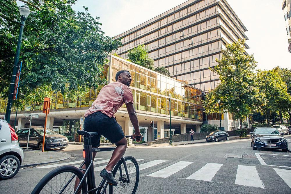 a man riding a Cowboy e-bike in a European city