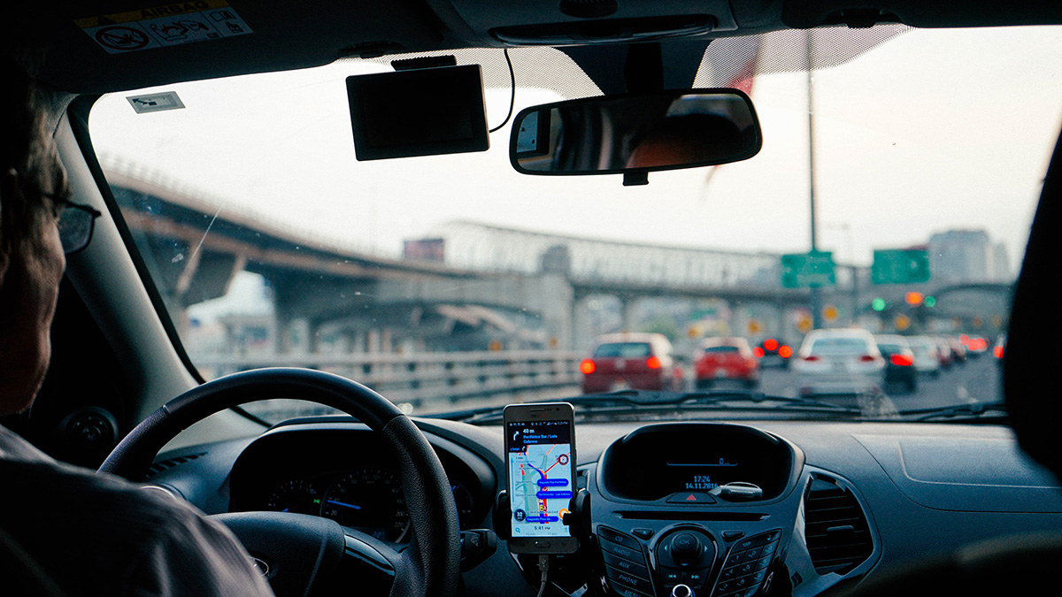 two drivers use a GPS app to navigate through traffic