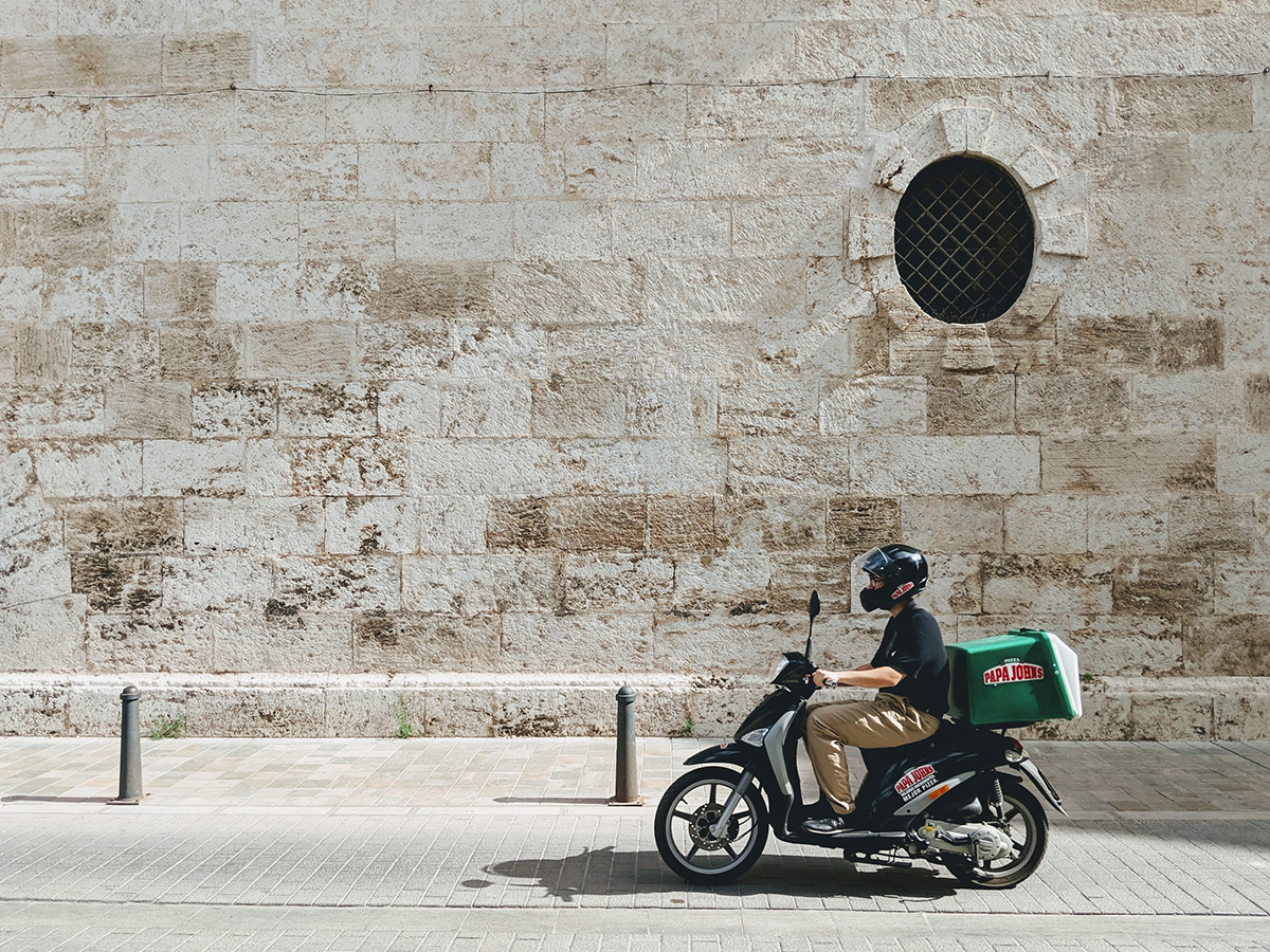 a pizza delivery driver rides his motorbike through a European city