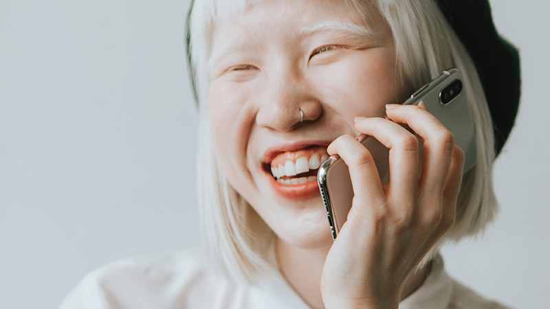 a happy young person smiling as they talk to someone on their iPhone