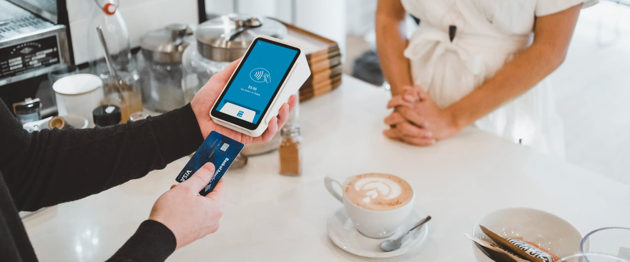 a consumer using a credit card to check out at a coffee shop